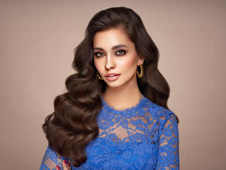 Brunette girl with perfect makeup. Smiling beautiful model woman with long curly hairstyle. Care and beauty hair products. Model in blue dress