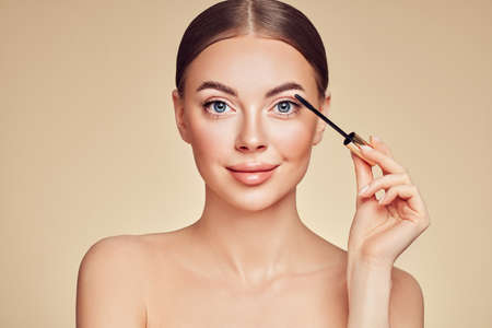 Beauty woman applying black mascara on eyelashes with makeup brush. Eyelash extensions. makeup, cosmetics. beauty, skincare