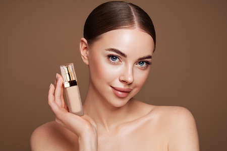 Portrait beautiful young woman with clean fresh skin. Model with foundation makeup bottle. Cosmetology, beauty and spa