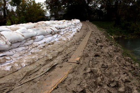 levy: Sandbags flood protection on a muddy levy with trail made from wooden planks