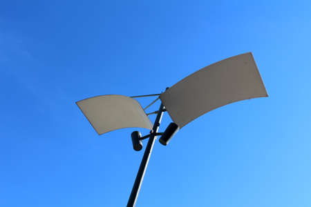 them: Modern LED lamp post with two reflecting panels and two LED lamps pointed at them. All under clear blue sky on a warm sunny day
