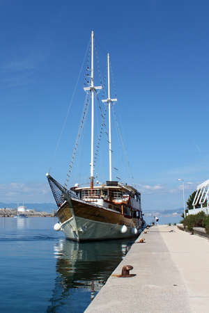 mooring bollards: Vintage sailboat docked on local pier and tied with thick sailor rope to iron mooring bollards. Calm sea reflects clear blue sky Stock Photo