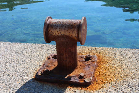 Strong, but rusted old iron mooring bollards on local concrete and stone pier with calm blue sea in background Stock Photo