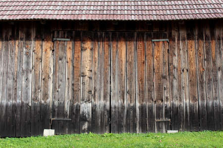 Large unpainted wooden barn doors with strong metal hinges, red roof tiles and uncut grass in front on warm sunny day