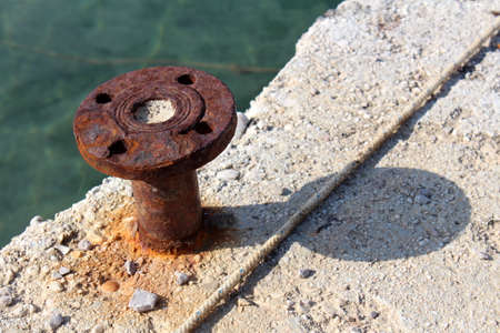 Rusted old iron mooring bollards mounted on concrete pier with shadow, rope and calm sea in background