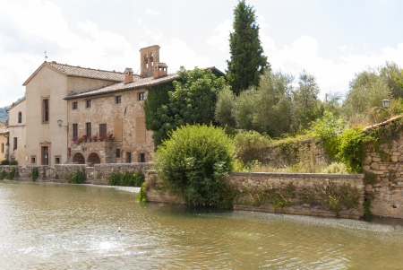 aquifer: Bagno VIgnoni, medieval town in Tuscany  The heart of the village with the   Square of sources , a rectangular tank with the original source of water  comes from the underground aquifer of volcanic origins and the Church of St  John the Baptist  Stock Photo