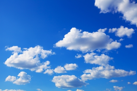 A horizontal shot of bright blue sky with puffy white clouds