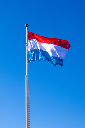 Waving flag of dukedom Luxembourg under blue sky