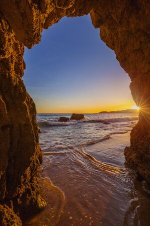 View from the beach through a rock formation to the Atlantic ocean, sunset at Algarve coast, Portugal
