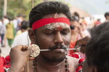 PANGKOR ISLAND, MALAYSIA - February 17, 2011, Masi Magam festival. Some devotees pierce their cheeks or tongue with arrows or spears.