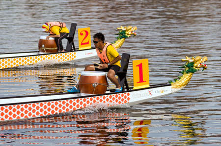 june 18, 2010 : During the races, dragon boat teams paddle harmoniously and hurriedly, accompanied by the sound of beating drums during the dragon boat festival on Putrajaya Lake, Kuala Lumpur, Malaysia