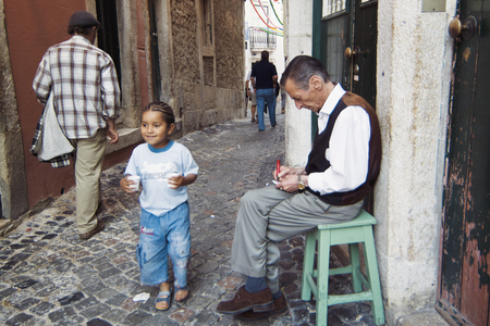 LISBON, ALFAMA, PORTUGAL - june 15, 2005 :  a fado singer waits his turn in front of a cafe in which he is going to perform in the evening