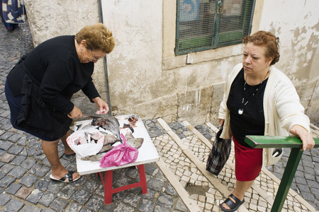 LISBON, ALFAMA, PORTUGAL - june 15, 2005 :  the fish merchants set up their little stall on the stairs of Alfama
