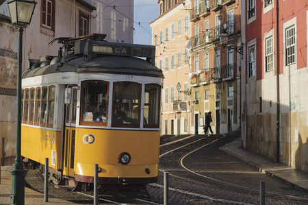 LISBON, ALFAMA, PORTUGAL - june 15, 2005 :  the famous tramway number 28 pass Rua Limoeiro in the top of Alfama Editorial