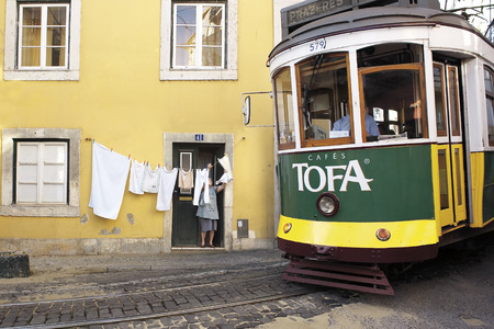 LISBON, ALFAMA, PORTUGAL - june 15, 2005 :  the famous tram number 28 pass Rua Sao Tome in the narrow streets of the Alfama Editorial