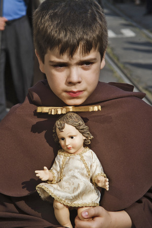 LISBON, ALFAMA, PORTUGAL - june 15, 2005 : a young boy holds the statue of an angel at the passage of the procession of St. Anthony Editorial