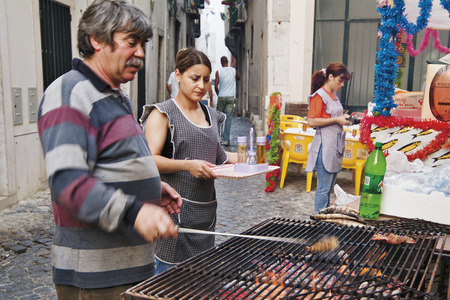 LISBON, ALFAMA, PORTUGAL - june 15, 2005 : during the feast of St. Anthony in the alleys eat sardines