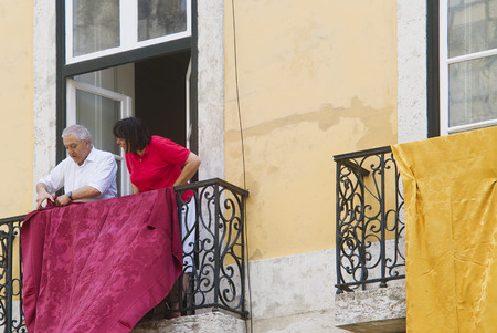 LISBON, ALFAMA, PORTUGAL - june 15, 2005 : the inhabitants of Alfama hoist precious textiles on their balcony in the passage of the procession of St. Anthony
