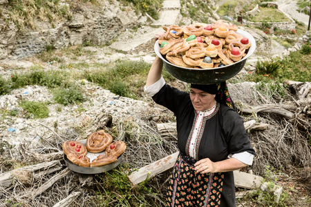OLYMPOS, KARPATHOS island – april 23, 2008 : Easter, a woman picks up all the buns decorated with a red egg Editorial