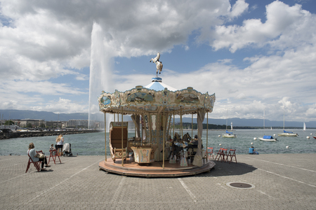 Geneva, Switzerland - june 01, 2018 : beautiful sunny day onon a carousel very old, decorated with Swiss landscapes and placed on the dock that leads to the jet of water Editorial