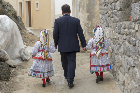 A father accompanies his two daughters to the village hall during the Easter holidays in Olympos village, Karpathos island Greece
