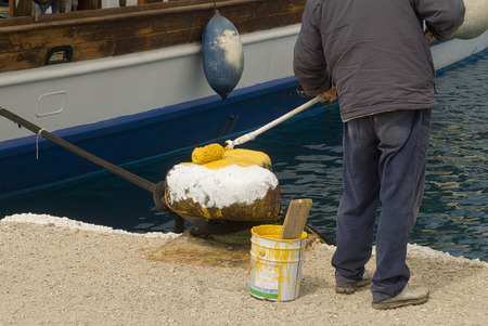 Greece, Pigadia, November 10, 2009 : A worker repaints the mooring spots in white on the pier of Pidadia