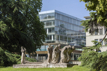 Geneva, Switzerland - june 10, 2018 : The new building of the World Trade Organization (WTO) and in the park, the sculpture, entitled Editorial