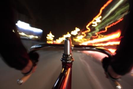 長い露出をカメラから撮影された固定フォアハンドで固定ギアの自転車に乗って近くハンドルバーの 写真素材