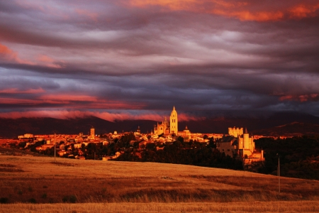 A medieval town pops up in the the middle of the countryside illuminated by the sunset light  Over the city a grey and purple colour cloudy sky  photo