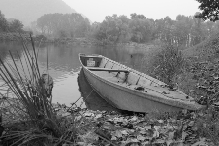 landfall: Black and white image of a boat left on the shore of a river Stock Photo