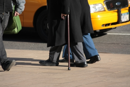 New York City, NY, USA – January 20, 2013  Senior Citizen walking with the aid of a cane beside a carer, Lincoln Square   Editorial