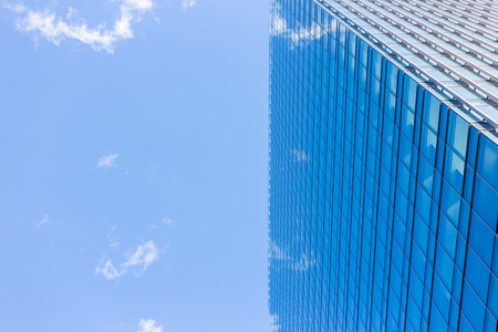 The wall of an urban building shows a blue sky and white cloud