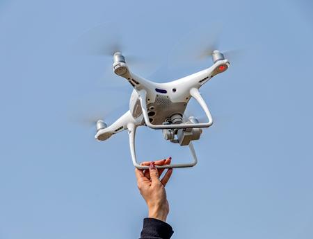 Womens hand catching drone Imagens