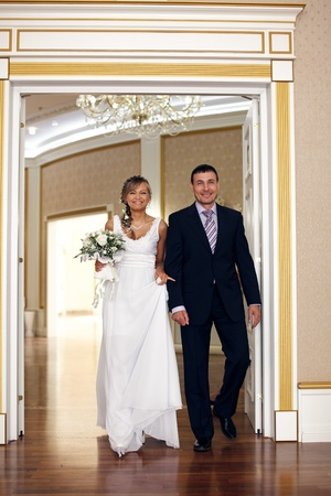 come in: Happy bride and groom come in the hall