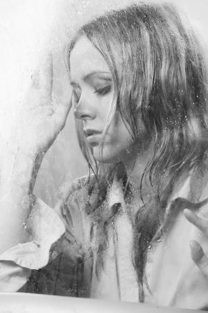 Beautiful woman behind wet glass photo