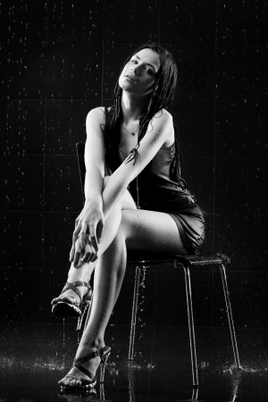 Young sexy woman sitting. Water studio photo. Black and white photo