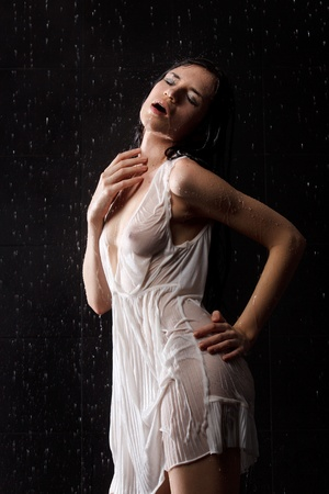 Sexy woman in water studio in white dress photo