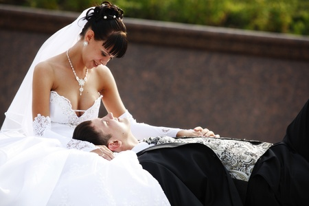 Bride sitting and groom laying in the park photo