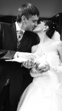 Black and white portrait of bride and groom kissing and holding pigeons photo