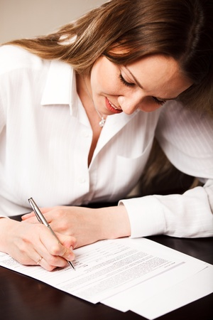Attractive young woman signing contract photo