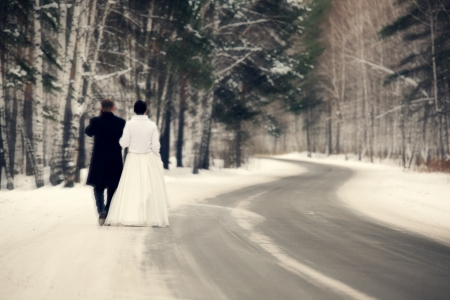 Newlyweds walks away outdoors. Road in the forest photo