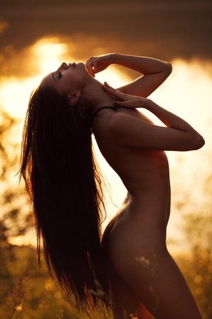 Portrait of a naked girl on a lake. In rays of sunset