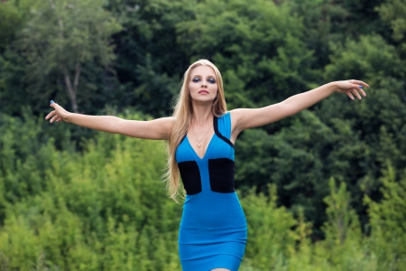Young woman standing on the fild with her arms outstretched photo