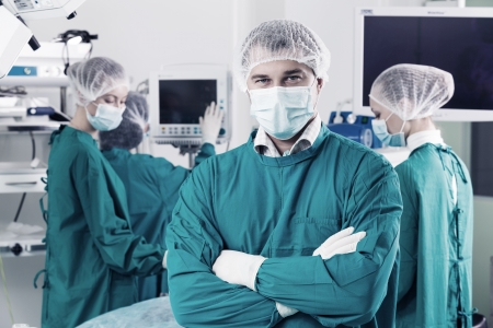 Surgeon with arms crossed looking at camera with colleagues performing in background photo