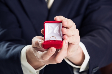 Close up of man holding wedding ring and gift box. Imagens