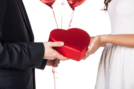 Gift. Surprise. Couple holding present and balloons photo