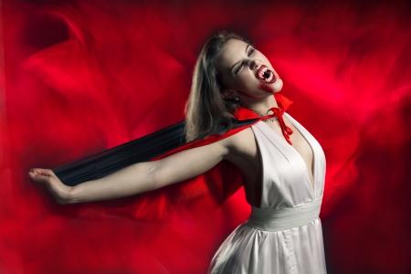 vampira sexy: Chica sexy vampiro sobre fondo rojo