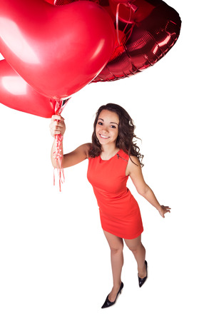 Valentines day. Woman smiling holding red heart shaped balloon. photo