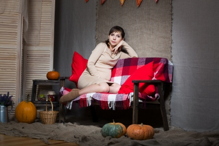 Young pregnant woman sitting on sofa photo