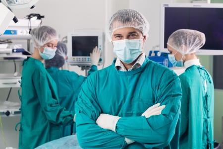 cirujano: Cirujano con los brazos cruzados mirando a la c�mara con sus colegas realizando en segundo plano